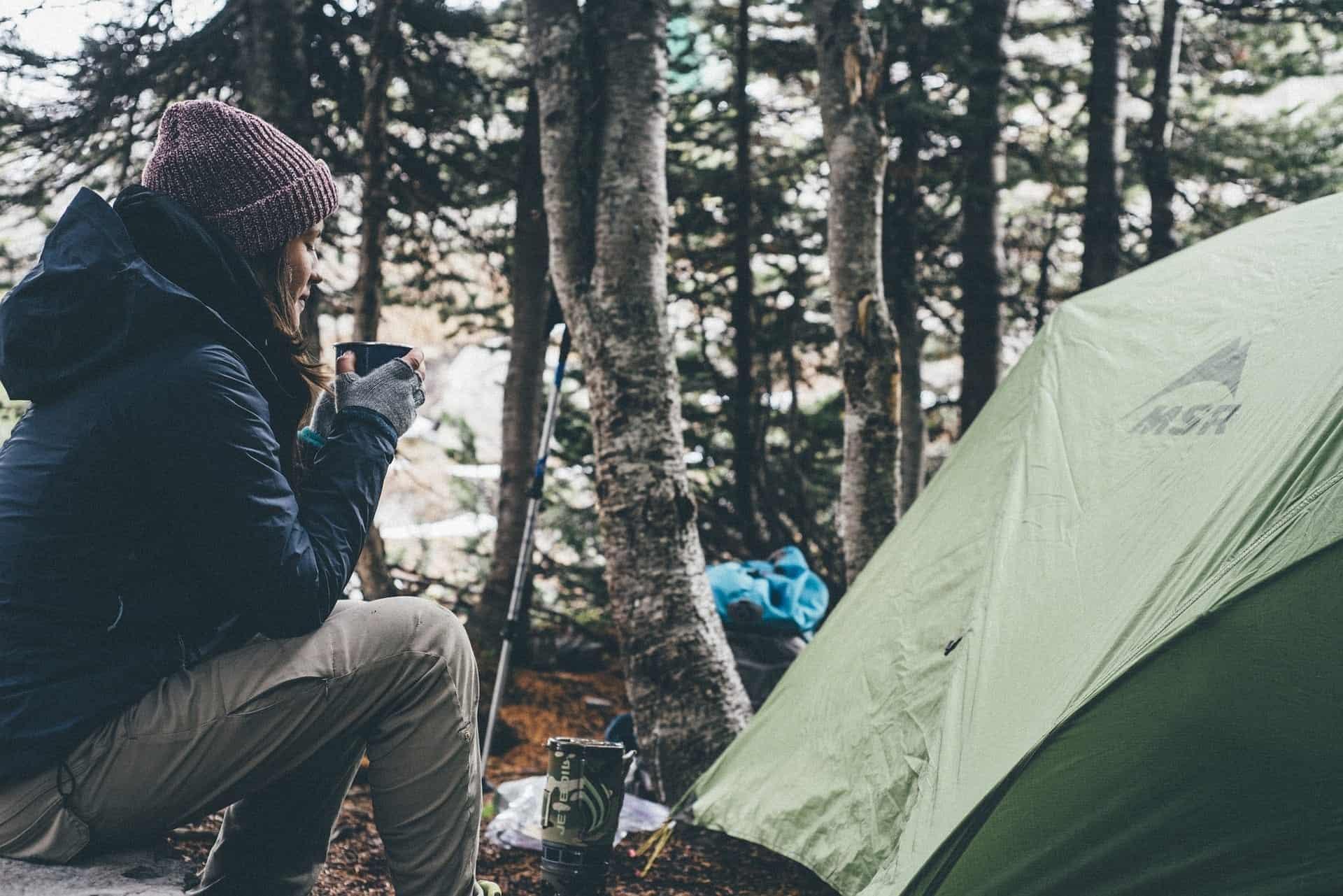 Frau mit Tasse vor dem Zelt im Wald
