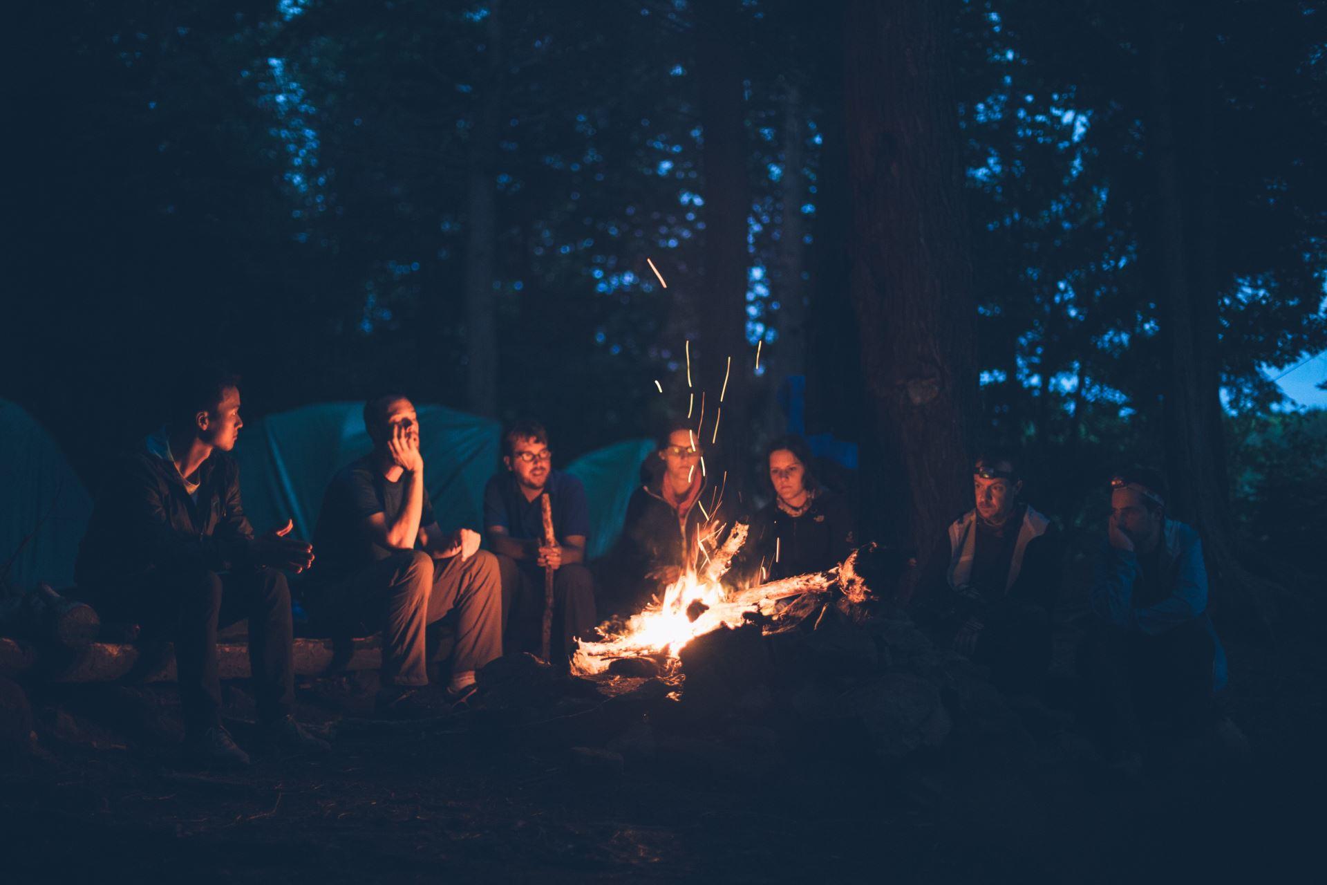 Menschen sitzen am Lagerfeuer
