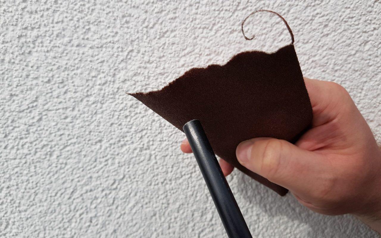 Die Splitter von der Schnittkante mit Schleifpapier entfernen