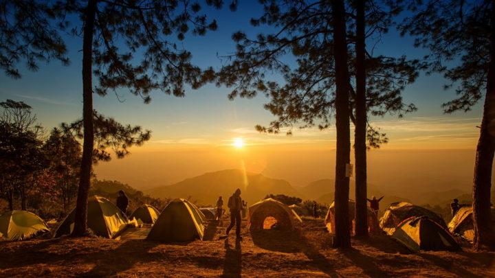 Mehrere Zelte auf einem Berg im Sonnenuntergang