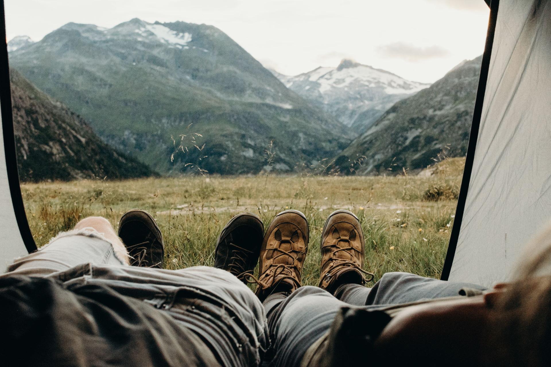 Zwei Camper liegen im Zelt in den Bergen