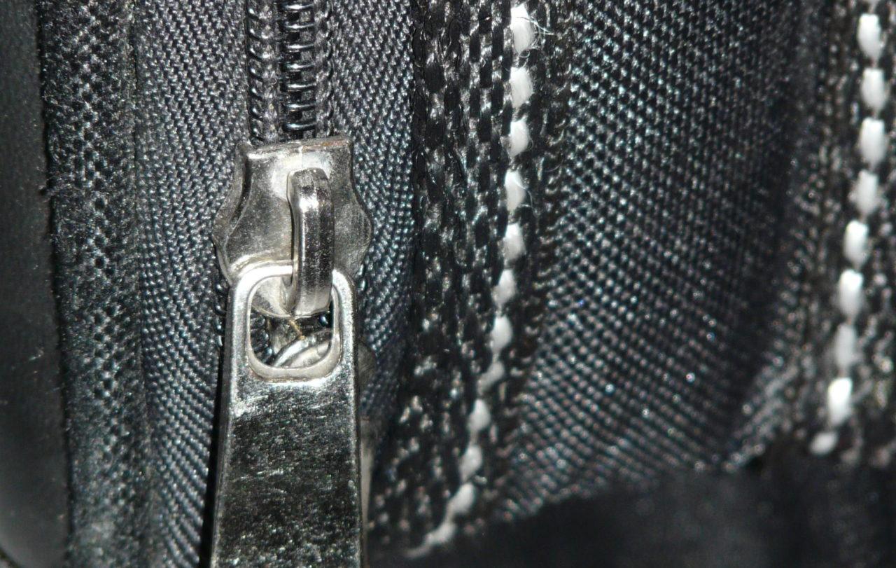 Ein geschlossener Reißverschluss auf schwarzem Stoff