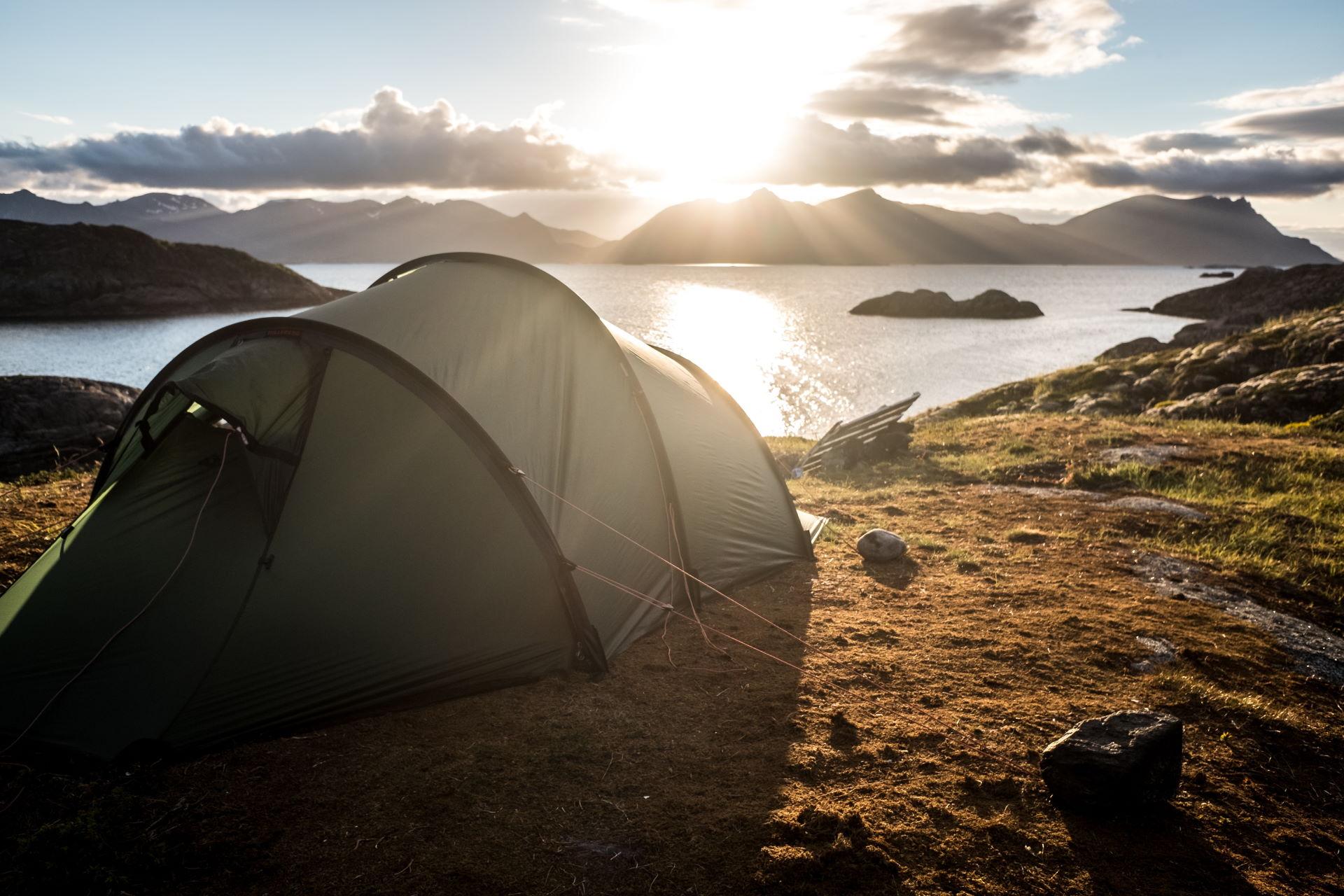 Ein Tunnelzelt steht auf einem Berg am Meer bei Sonnenaufgang