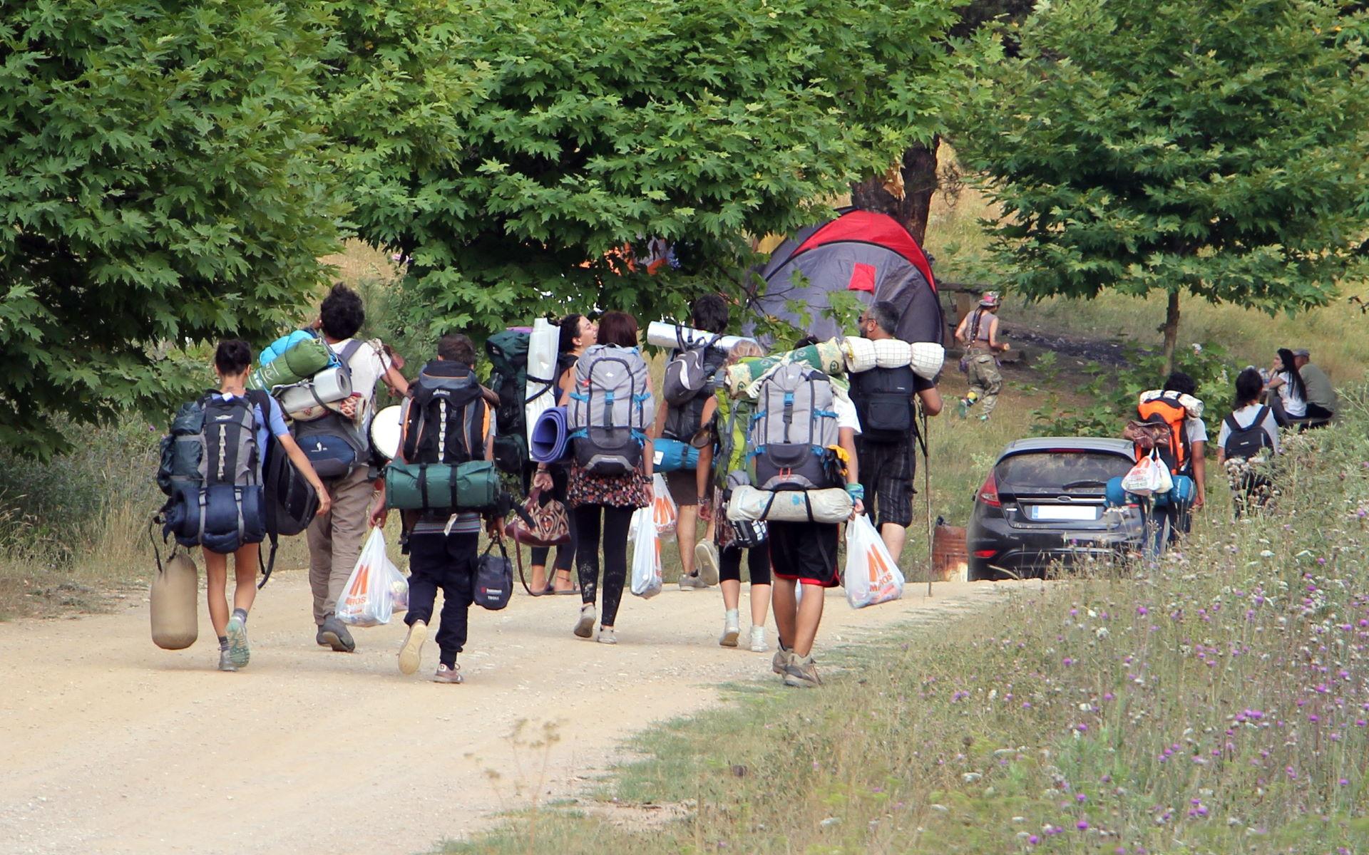 Menschen mit Rucksäcken, Zelten und Schlafsäcken laufen einen Weg entlang