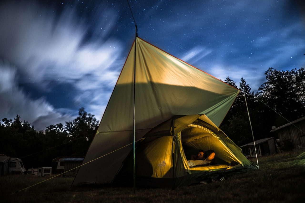 Mann liegt im Zelt unter einem Tarp bei Nacht