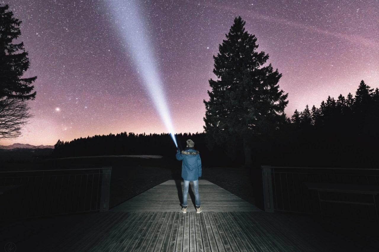 Mann steht mit einer Taschenlampe auf einer Brücke bei Nacht