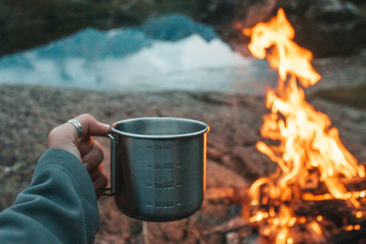 Am Lagerfeuer die Natur mit einer heißen Tasse Kaffee genießen