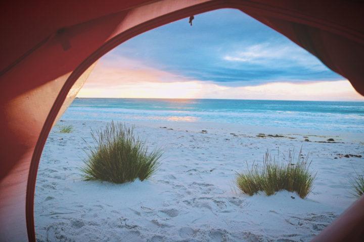 Blick aus einem Zelt am Strand in den Sonnenaufgang