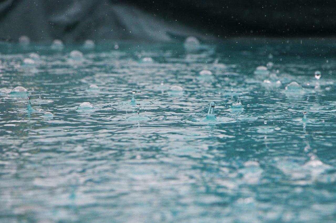 Zelten bei Regen - Regentropfen auf dem Wasser
