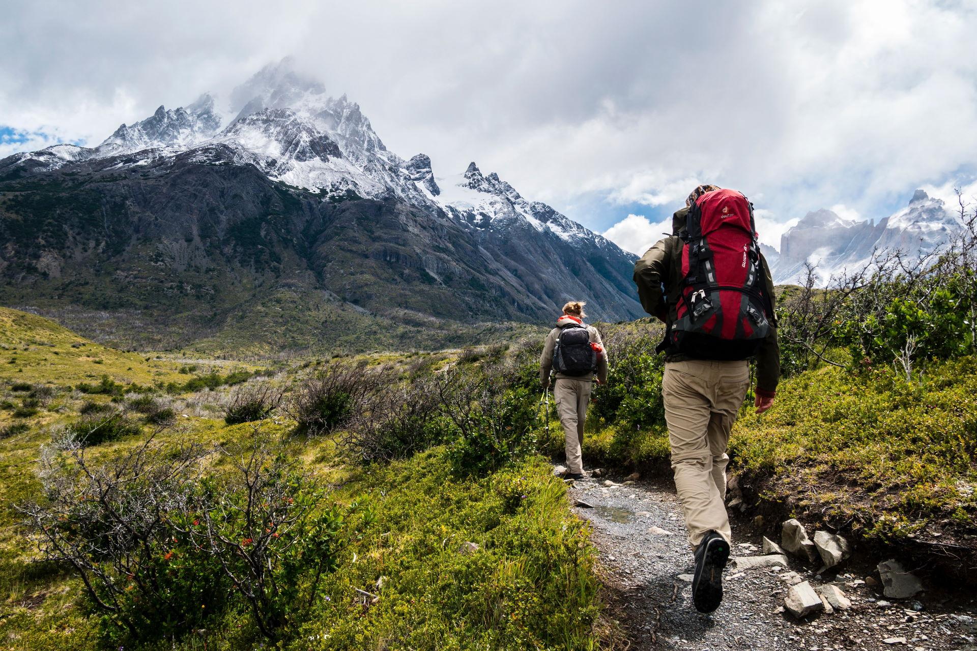 Zwei Wanderer auf einem nassen Weg im Gebirge