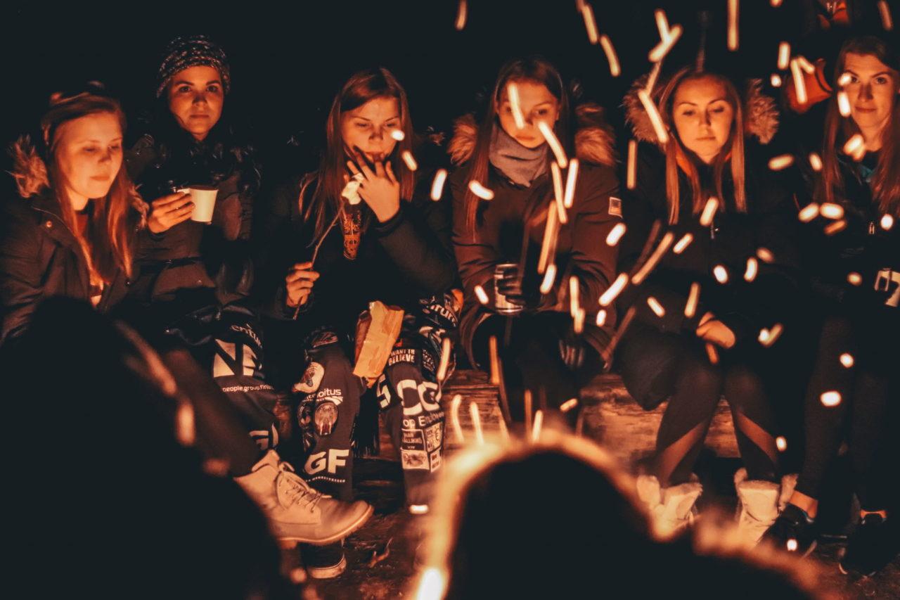 Frauen sitzen an einem Lagerfeuer