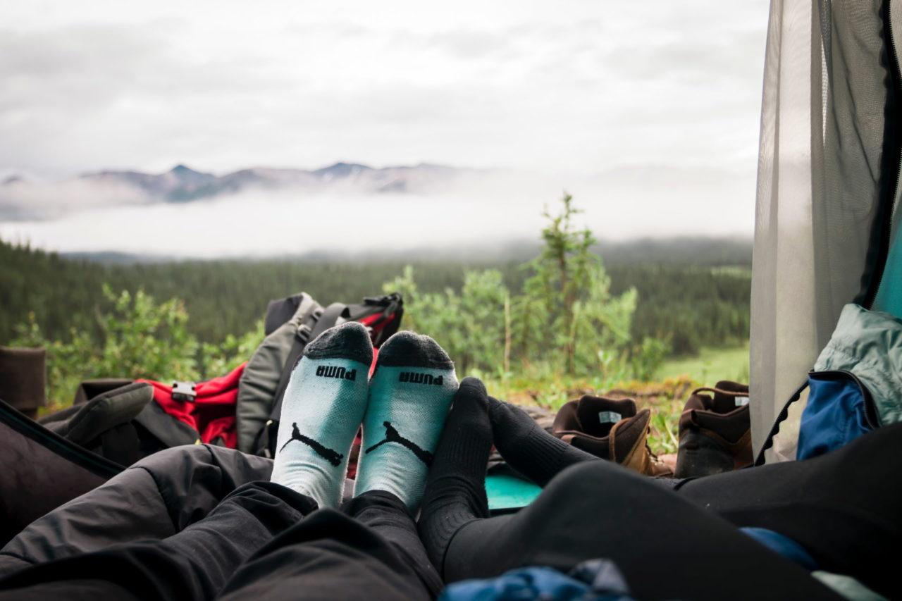 Menschen liegen im Zelt vor einem Berg