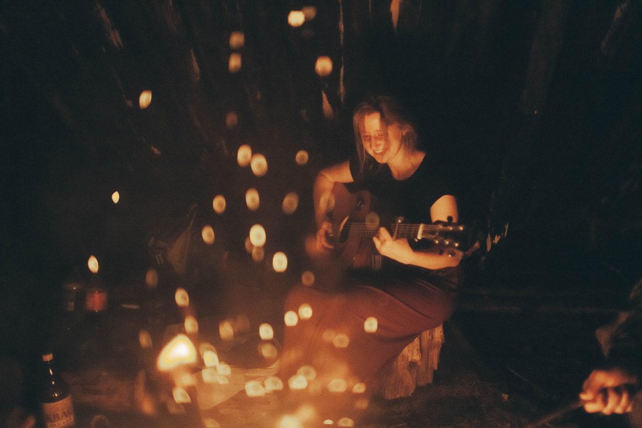 Frau spielt am Lagerfeuer ein Lied auf der Gitarre und singt mit