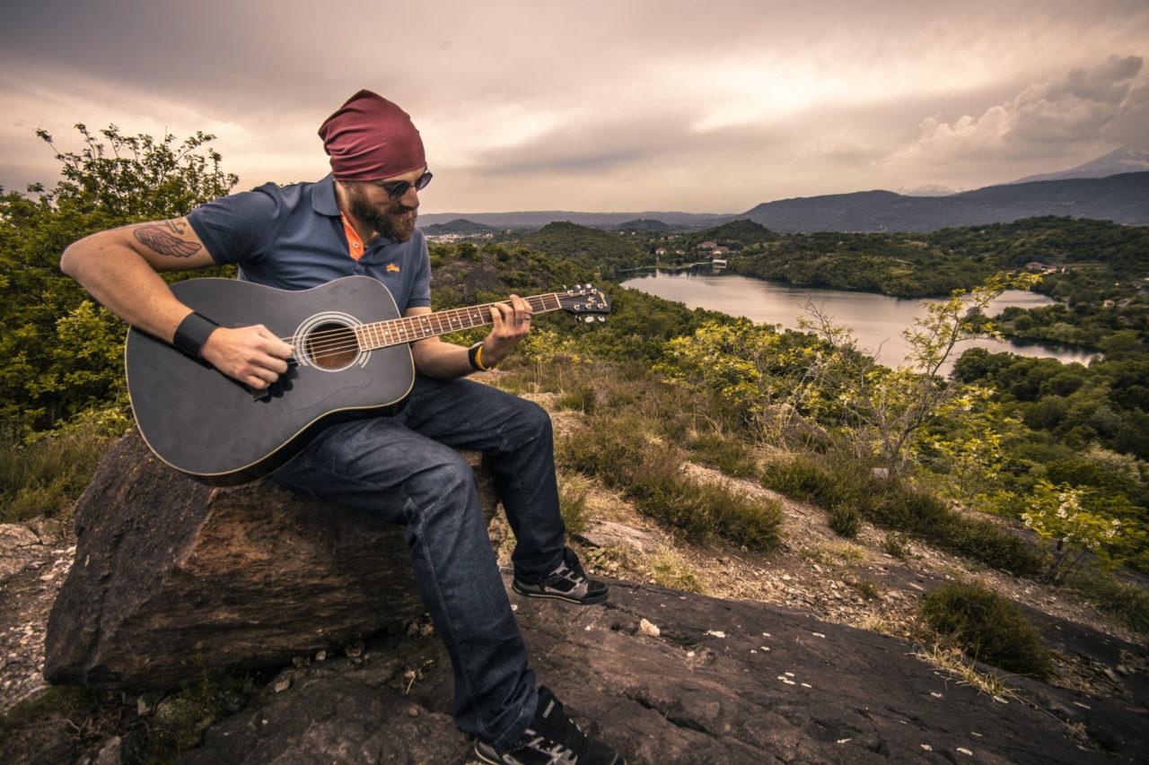 Mann mit Gitarre sitzt auf einem Felsen am See und spielt