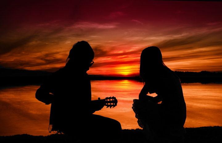 Mann und Frau mit Gitarre im Sonnenuntergang