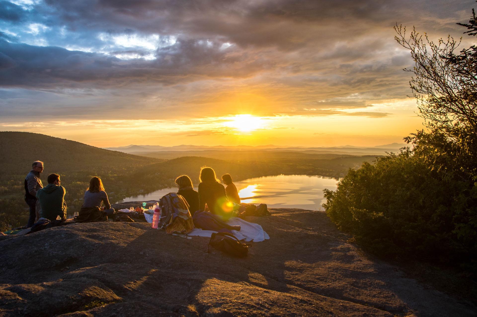 Menschen machen ein Picknick auf einem Berg und schauen auf einen See in den Sonnenuntergang [Camping, Zelten, Outdoor]