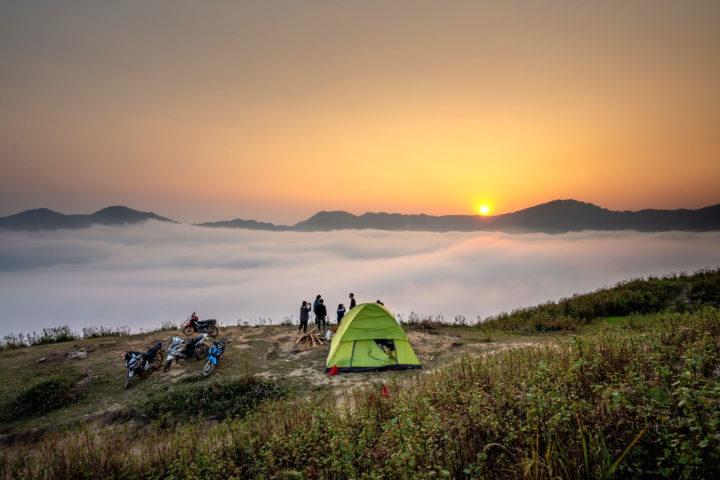 Menschen stehen neben einem grünen Zelt auf einem Bergrücken