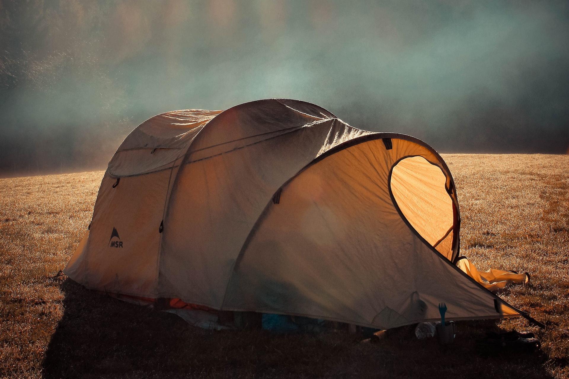 Ein braunes Zelt steht auf einer nebeligen Wiese