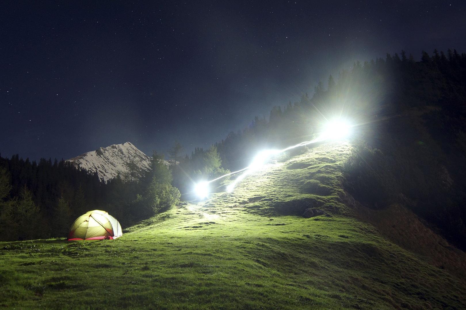 Erleuchtetes Zelt bei Nacht mit großen Scheinwerfern im Gebirge