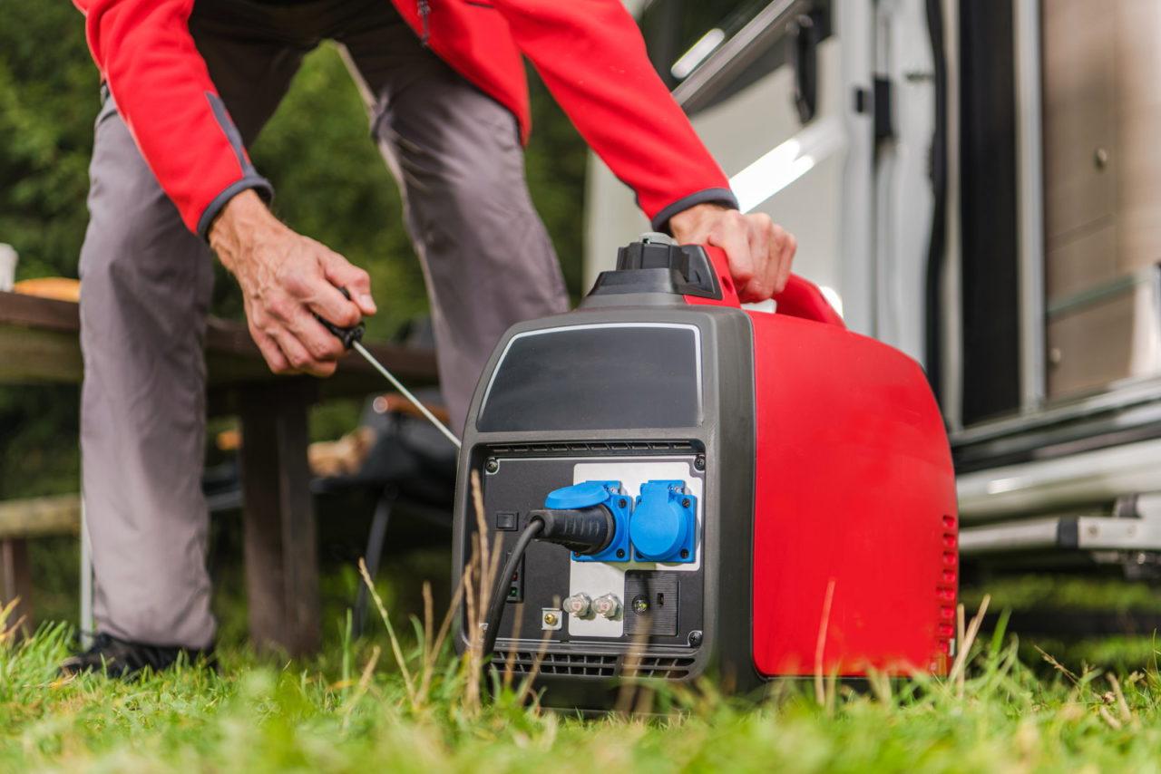 Mann startet einen roten Inverter Stromerzeuger neben einem Wohnmobil