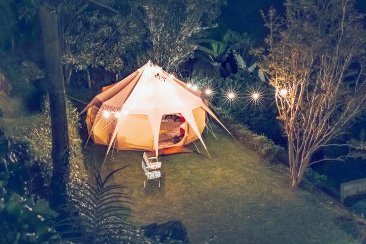 Mit einer Lichterkette beleuchtetes Zelt im Wald bei Nacht