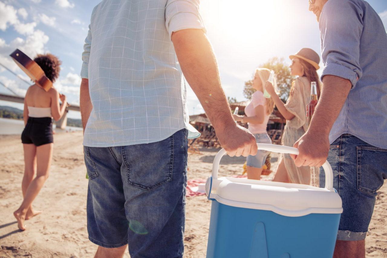 Zwei Männer tragen eine blaue Kühlbox zum Strand