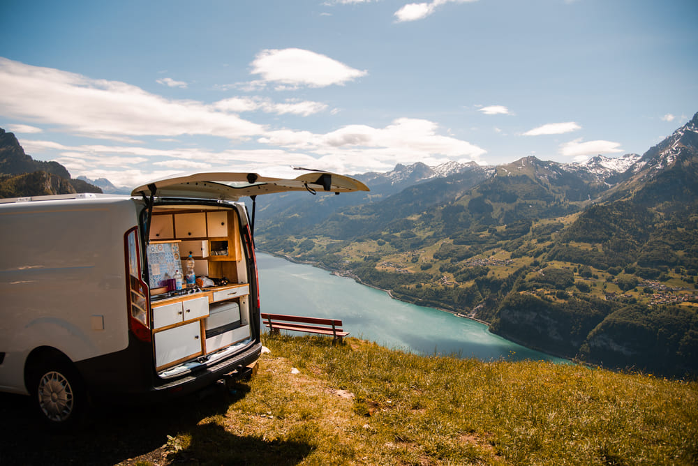 Campervan mit offener Heckklappe an Bergsee