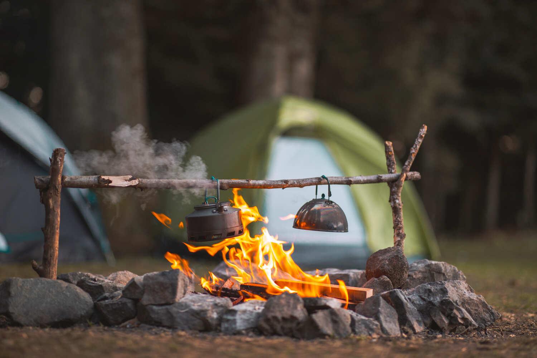 Lagerfeuer und Teekessel mit Kuppelzelt im Hintergrund