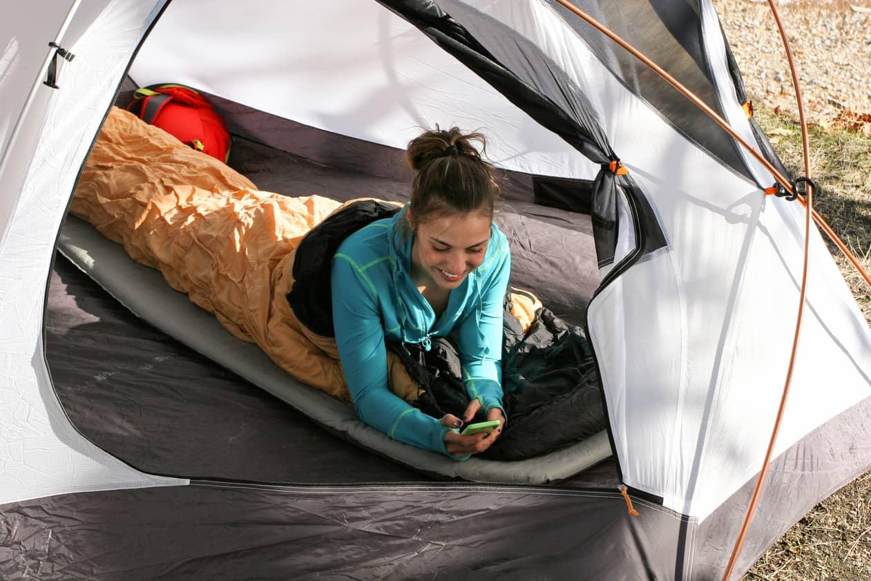 Frau liegt im Schlafsack im Zelt